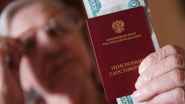 Женщина держит пенсионное удостоверение