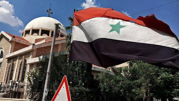 Государственный флаг Сирийской Арабской Республики у православной церкви в старом христианском квартале города Алеппо