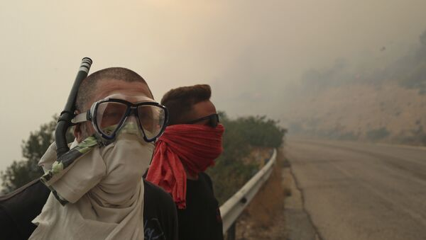 Люди закрывают лица от дыма во время лесного пожара возле Кинеты, к западу от Афин. 23 июля 2018 года