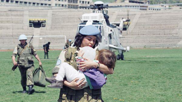 Женщина-солдат ООН несет двухлетнюю девочку, которую эвакуировали из города Горажде в Сараево, 25 апреля 1994 года