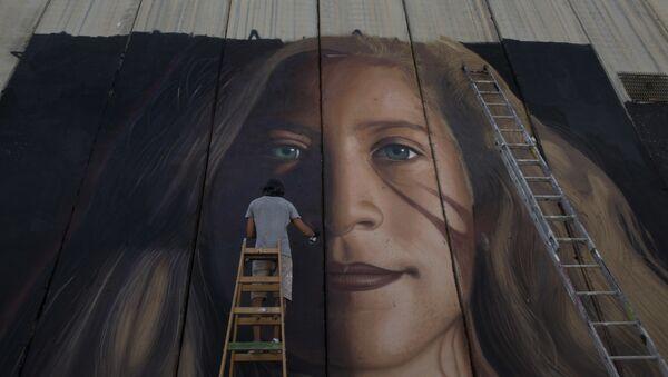 Гигантский мурал с портретом палестинской активистки Ахед Тамими на части израильской разделительной стены в городе Вифлеем на Западном берегу. 25 июля 2018