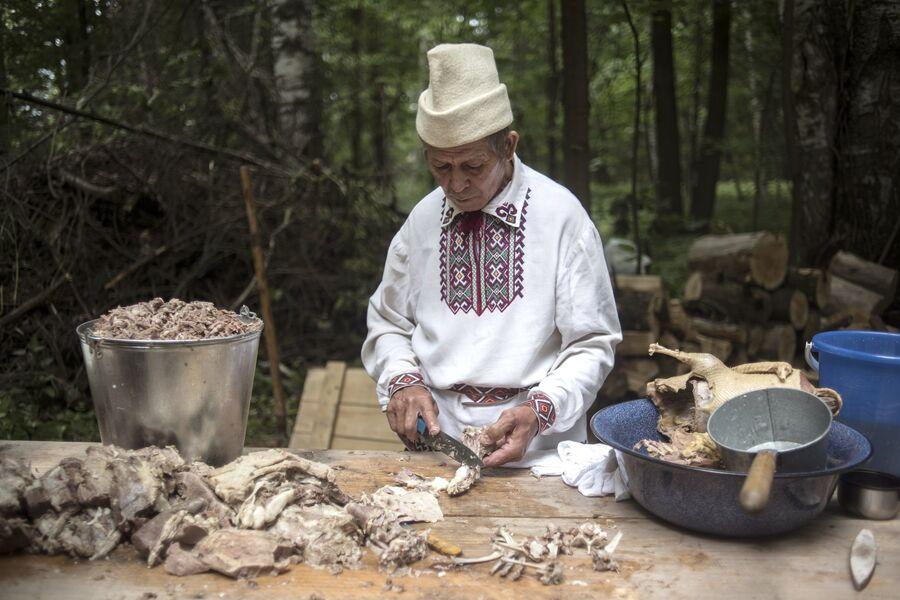Житель села Шоруньжа во время приготовления ритуального яства на празднике Сярем