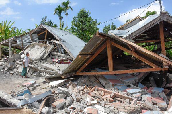 Местный житель осматривает разрушенный землетрясением дом на острове Ломбок в Индонезии.