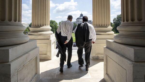 Конгрессмены покидают здание Капитолия в Вашингтоне после окончания голосования в Палате представителей