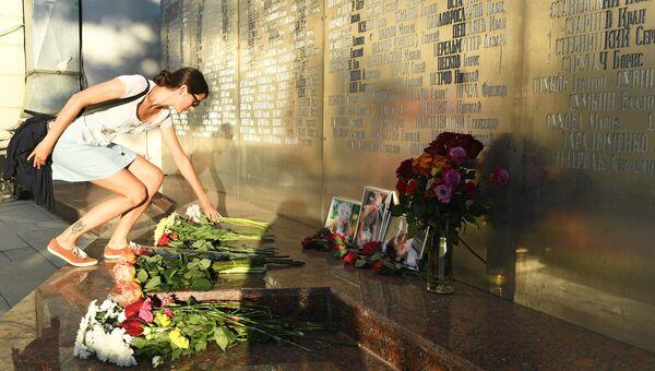 Девушка возлагает цветы у фотографий погибших в Центральноафриканской Республике  журналистов возле Дома журналистов в Москве