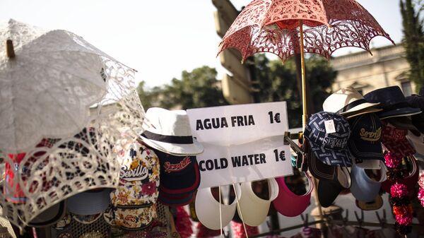 Продажа зонтиков, кепок и шляп на улице города Севилья в Испании. 4 августа 2018