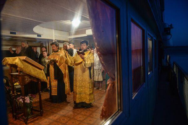 Священнослужители духовно-просветительской миссии проводят службу на корабле-церкви Святой апостол Андрей Первозванный во время стоянки у села Каргаполово Новосибирской области