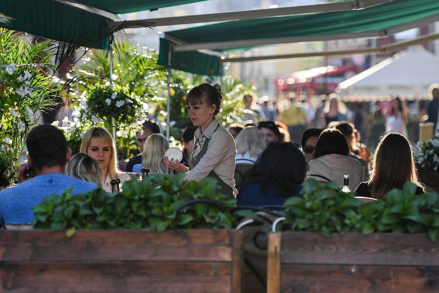Посетители в летнем кафе в Климентовском переулке в Москве