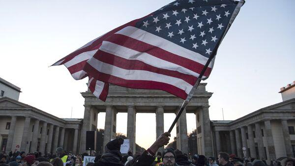 Флаг США во время акции протеста у Бранденбургских ворот в Берлине
