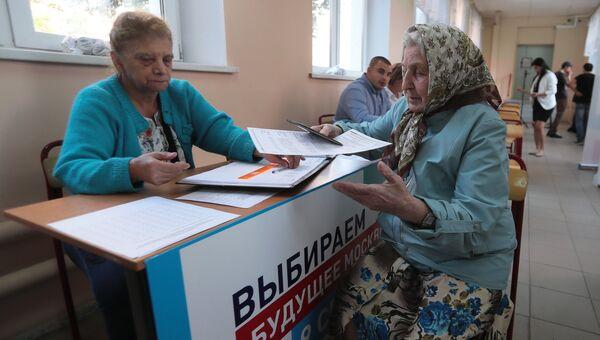 Избирательница и наблюдатель в единый день голосования на избирательном участке в Москве
