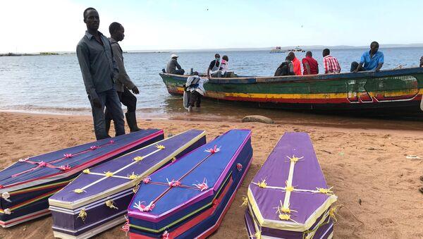 Волонтеры рядом с гробами погибших при опрокидывании парома рядом с островом Юкора на  озере Виктория, Танзания. 22 сентября 2018