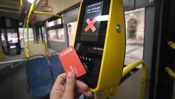 Пассажир прикладывает билет к валидатору в автобусе. Архивное фото