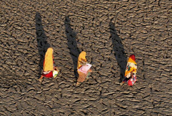 Женщины идут по берегу реки Ганг в Аллахабаде, Индия
