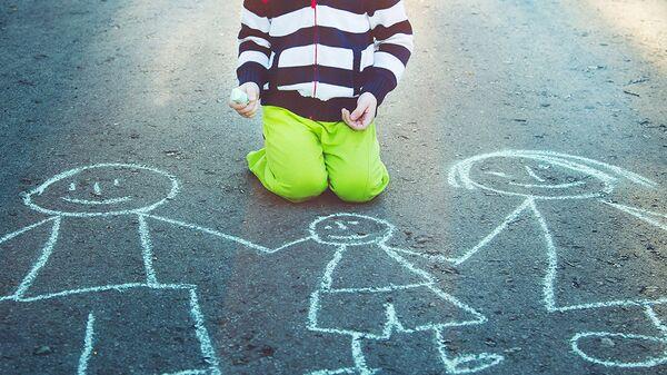Ребенок рисует на асфальте мелом