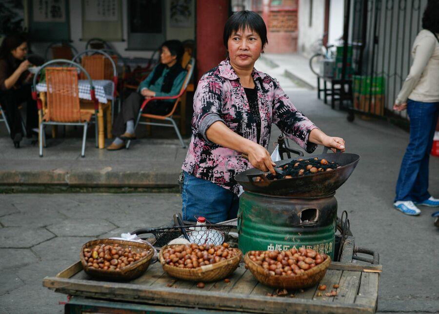Торговля жареными каштанами в Китае