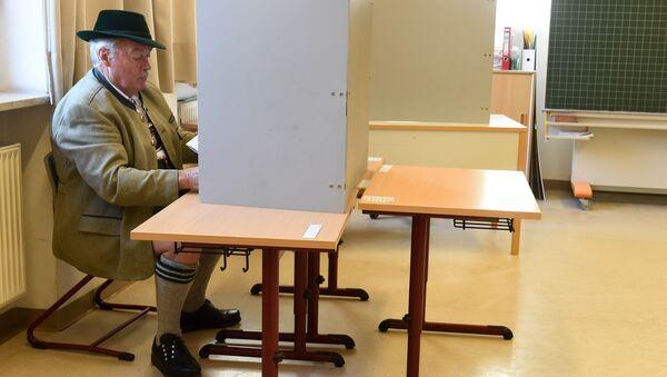 Мужчина в традиционной баварской одежде заполняет бюллетень для голосования на избирательном участке в Нойкирхене, Германия. 14 октября 2018