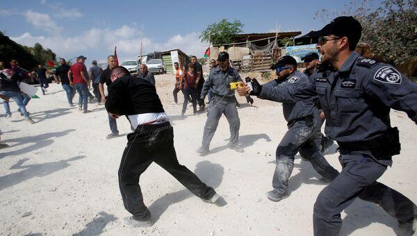 Израильские полицейские разгоняют активистов в палестинской деревне Бедуин Хана аль-Ахмара, которую Израиль планирует снести на оккупированном Западном берегу. 17 октября 2018