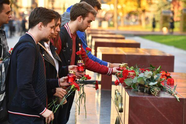 Люди возлагают цветы и ставят свечи на памятник городу-герою Керчи в Александровском саду в Москве в знак траура по погибшим при взрыве в колледже в Керчи