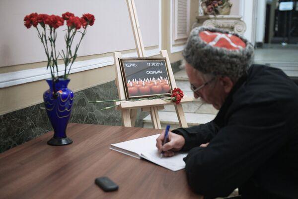 Мужчина оставляет запись в книге соболезнований в Санкт-Петербургском Доме национальностей в связи с происшествием в Керченском политехническом колледже