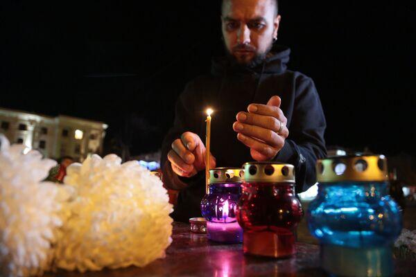 Мужчина зажигает свечу у народного мемориала в Симферополе в память о погибших при нападении на керченский колледж