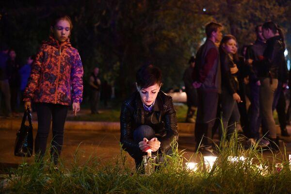 Женщина со свечой на улице в Керчи, где в Керченском политехническом колледже произошли взрыв и стрельба