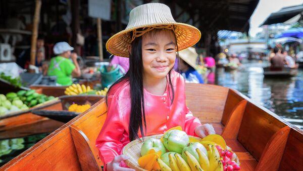 Девочка с корзиной фруктов на плавающем рынке в Таиланде