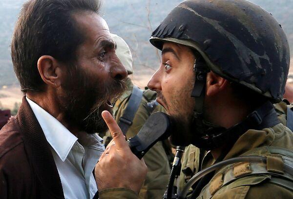 Палестинский мужчина спорит с израильским солдатом во время столкновений возле Наблуса на Западном берегу реки Иордан