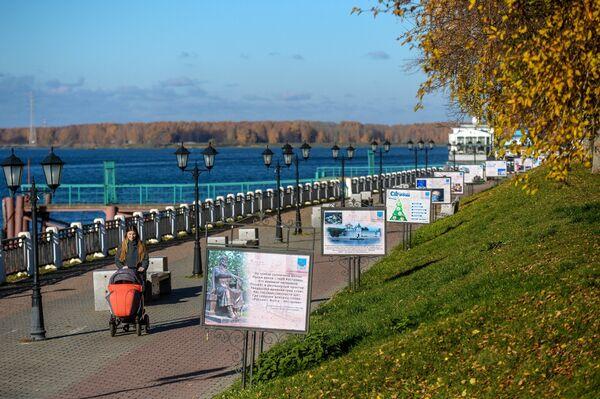 Девушка с коляской гуляет по набережной реки Волги в Костроме