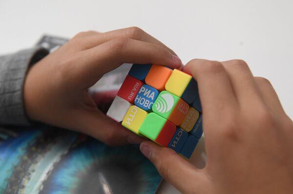 Кубик Рубика в руках посетителя стенда МИА Россия сегодня на всероссийском фестивале науки Nauka 0+ в фундаментальной библиотеке МГУ имени М. В. Ломоносова
