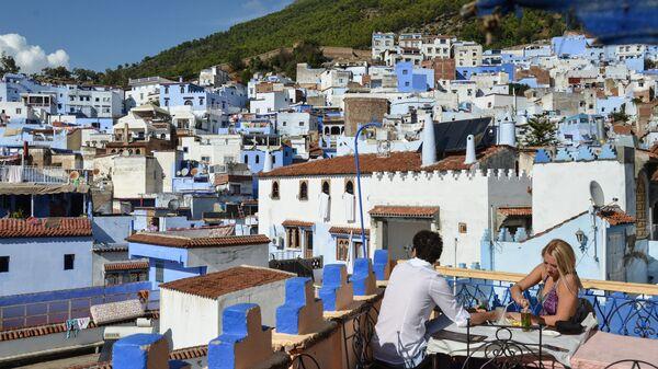 Люди в кафе на крыше одного из домов в городе Шифшавен, Марокко