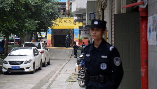 Полицейские у ворот детского сада, где женщина, вооруженная кухонным ножом, напала на детей, в Чунцине, Китай. 26 октября 2018