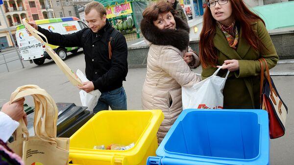 Горожане выбрасывают мусор в контейнеры раздельного сбора отходов