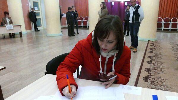 Девушка расписывается в списке избирателей во время голосования на выборах главы ДНР и депутатов Народного совета ДНР на избирательном участке в Донецке. 11 ноября 2018