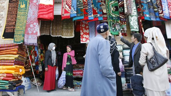 Уйгурские мусульмане выбирают молельные коврики на рынке в Хотане. Архивное фото