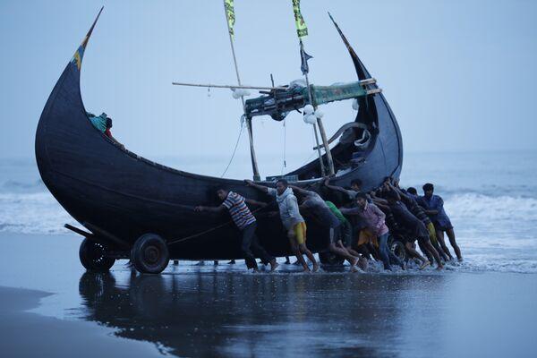 Рыбаки у лодки у берегов деревни Текнаф, Бангладеш