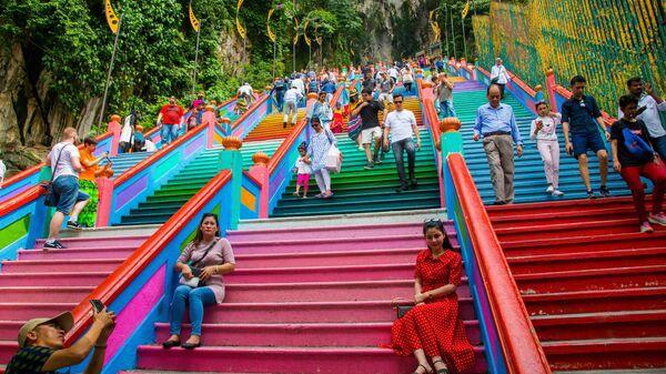 Туристы фотографируются на лестнице, ведущей в пещеры Бату в Куала-Лумпуре