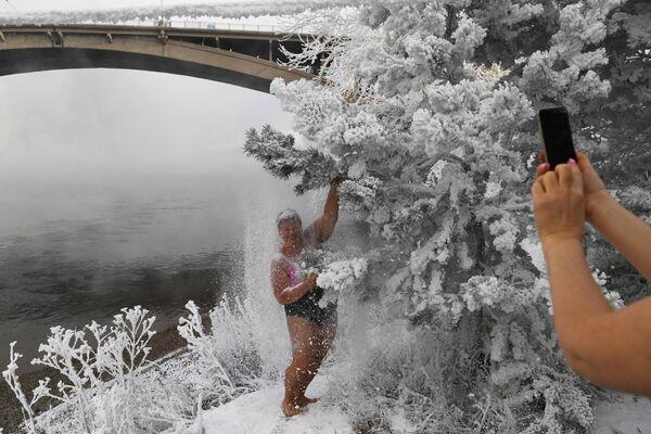 Участницы клуба зимнего плавания Криофил фотографируются у заснеженных деревьев на берегу реки Енисей в Красноярске