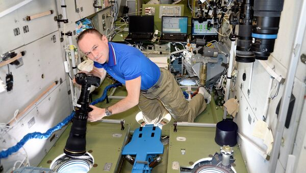 Космонавт Роскосмоса Сергей Рязанский фотографирует на борту МКС