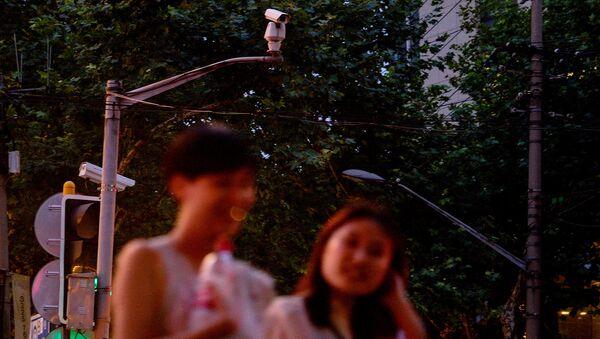 Камера с функцией распознавания лиц, которая следит за нарушениями правил дорожного движения, на улице Шанхая. Архивное фото