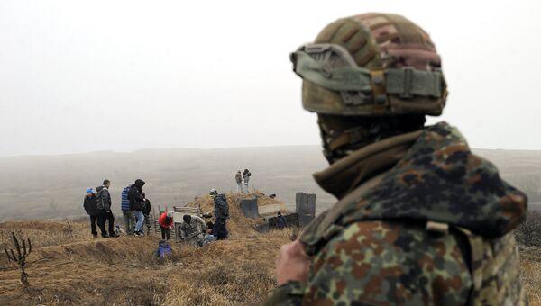 Украинский военнослужащий смотрит на активистов, копающих траншеи на побережье Азовского моря у города Мариуполь. 26 ноября 2018