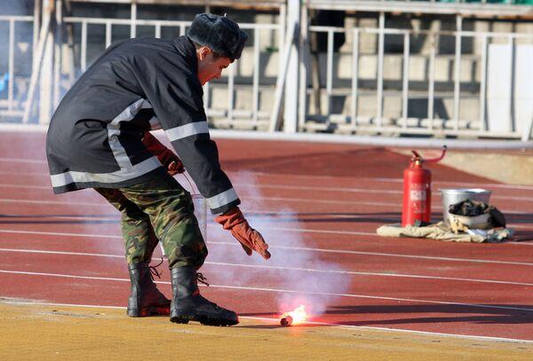 Сотрудник пожарной службы убирает брошенный на беговые дорожки файер.