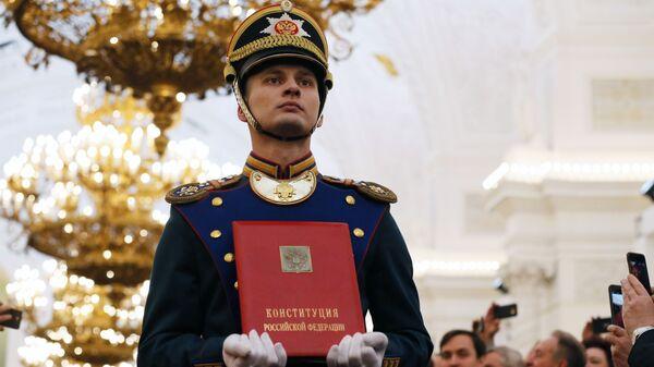 Солдат Президентского полка вносит специальный экземпляр Конституции России на церемонии инаугурации президента России Владимира Путина в Кремле. 7 мая 2018