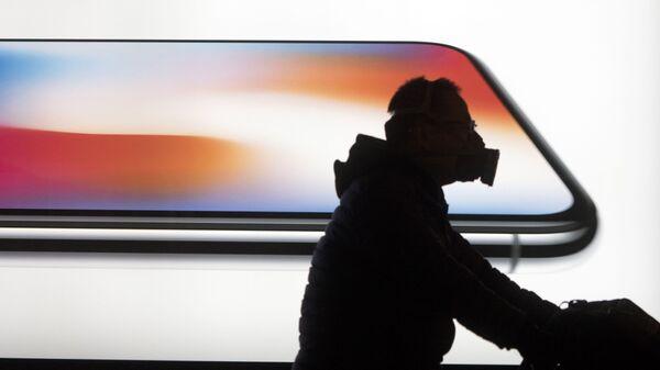 Мужчина на фоне рекалмы смартфона Iphone X в Пекине. КНР