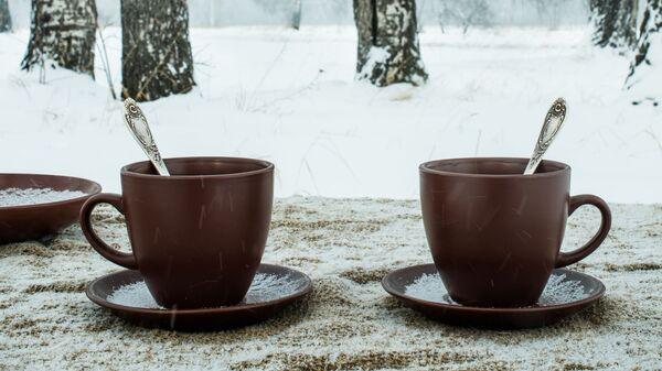 Две чашки на фоне зимнего пейзажа