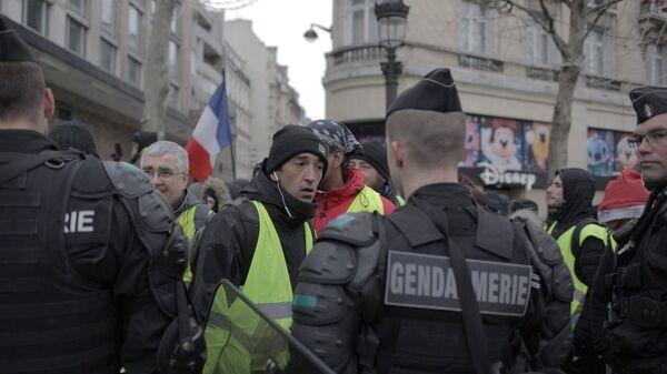 Сотрудники полиции и участники акции протеста движения автомобилистов желтые жилеты в районе Триумфальной арки в Париже