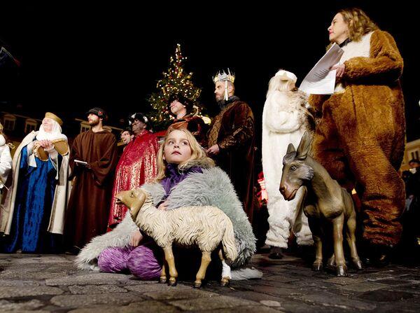Люди участвуют в спектакле на рождественском базаре в Гейдельберге