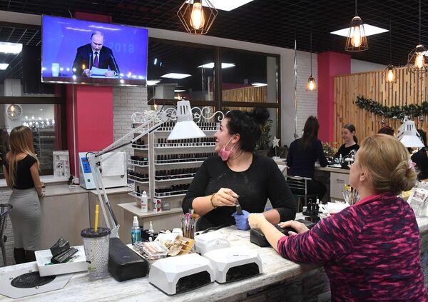 Женщины смотрят прямую трансляцию ежегодной большой пресс-конференции президента РФ Владимира Путина в салоне красоты во Владивостоке