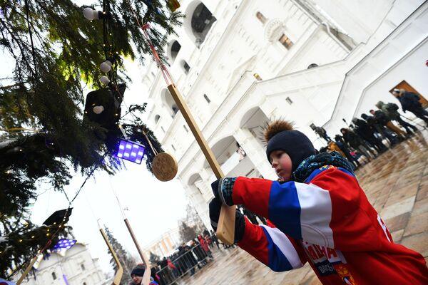 Ученик школы олимпийского резерва по хоккею украшает игрушечной клюшкой новогоднюю елку на Соборной площади Московского Кремля