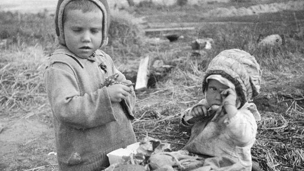 Дети у разрушенного дома в селе Мядель, Белоруссия