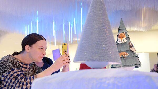 Посетитель фотографирует Левитирующую елку от Дома моды Алены Ахмадуллиной в парке Зарядье. 26 декабря 2018